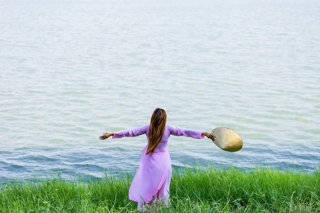Beautiful asian women vietnam look at the river and hat traditional ao dai. concept feeling relax and happy