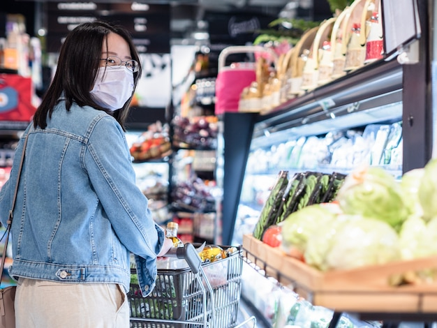 Beautiful asian women wear face mask with trolley in supermarket stand apart from other people for keeping safety social distancing as new normal lifestyle concept