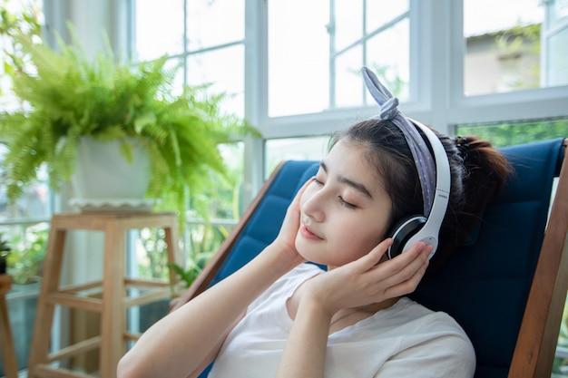 美しいアジアの女性は、ヘッドフォンを着用し、ノートパソコンを使用して、自宅の庭で仕事をしたり、音楽を聴いたりして、リラックスした日を過ごします。