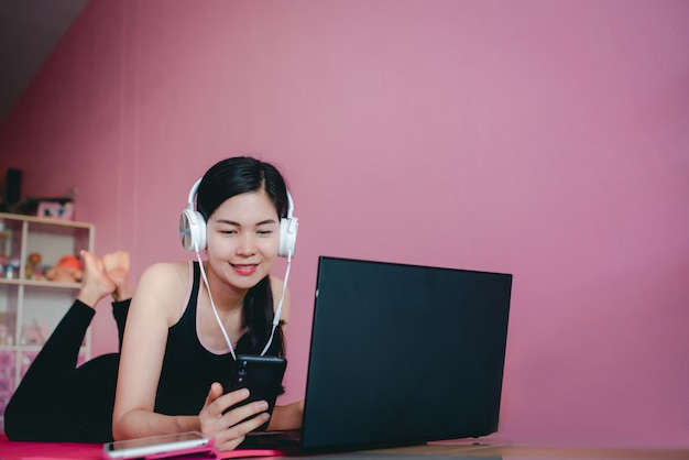 Beautiful asian women wear headphones, exercise in black sportswear, lie down, watch home exercise videos and notebook computers.