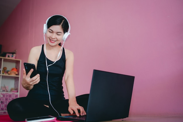 Beautiful asian women wear headphones to exercise in black sportswear, sitting watching videos, exercising at home and notebook computers.