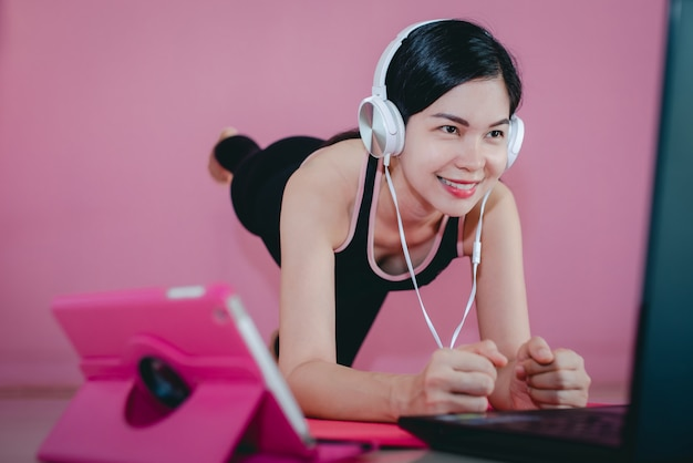 美しいアジアの女性は、ヘッドフォンを着用し、黒いスポーツウェアで運動し、横になり、自宅の運動ビデオやノートブックコンピューターを見ます。