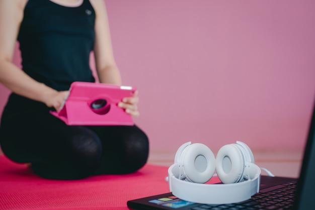 美しいアジアの女性はヘッドフォンを着用して黒いスポーツウェアで運動し、座ってビデオを見たり、自宅やノートパソコンで運動したりします。
