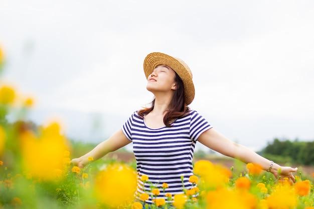 ぼやけた自然シーンの写真の投稿ビンテージ帽子をかぶっている美しいアジアの女性。黄色の花畑でかなりアジアの少女の肖像画をクローズアップ。