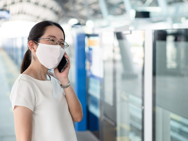 Beautiful asian women wearing disposable medical face mask, using smartphone while waiting for metro at train station platform, as new normal trend and self-protection against covid19 infection.