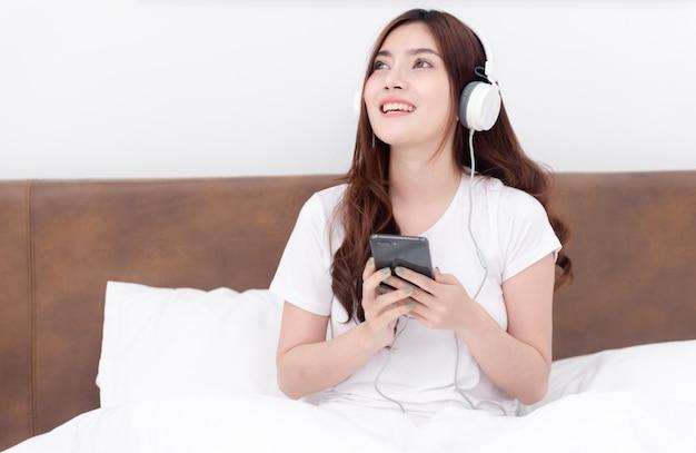 Красивые азиатские женщины в наушниках слушают музыку со своих смартфонов.