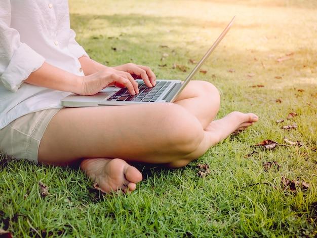 緑の芝生に座っているラップトップコンピューターで白いシャツとショートパンツを着ている美しいアジアの女性。