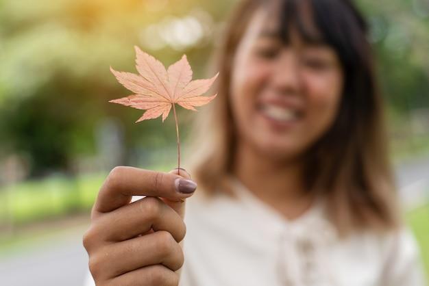 Красивые азиатские женщины в белых рубашках, держа красный кленовый лист, улыбаются, чувствуя себя счастливыми в саду.