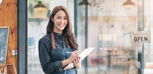 Красивая азиатская молодая женщина бариста в фартуке держа cllpboard и стоя перед дверью кафе с открытой доской знака. концепция запуска владельца бизнеса.