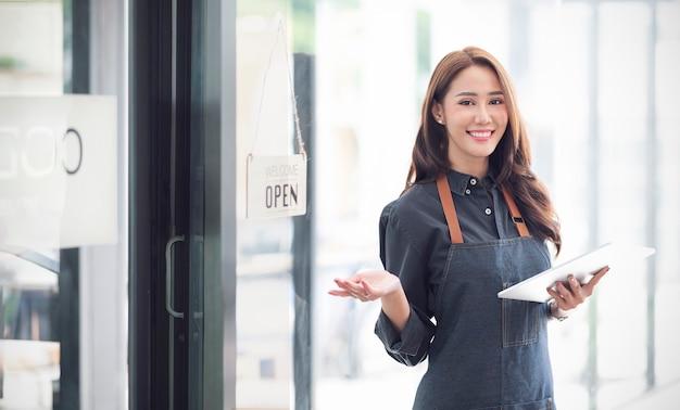 Красивая азиатская молодая женщина бариста в фартуке держа таблетку и стоя перед дверью кафе с открытой доской. концепция запуска владельца бизнеса.