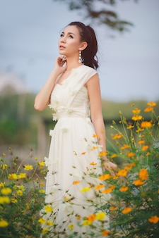 Beautiful asian young bride wearing white dress outdoors in a forest.