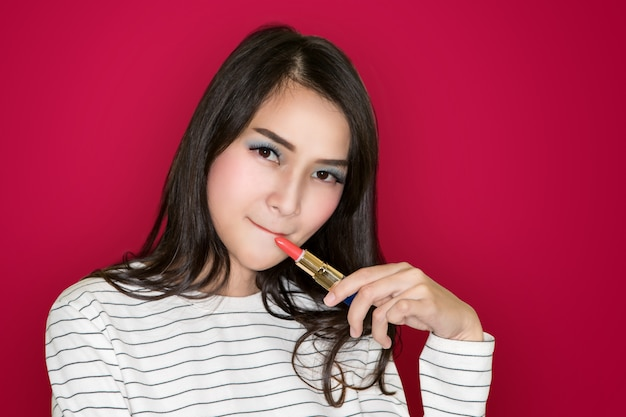 Beautiful asian young brunette girl with curly hair applying pink lipstick on pink background