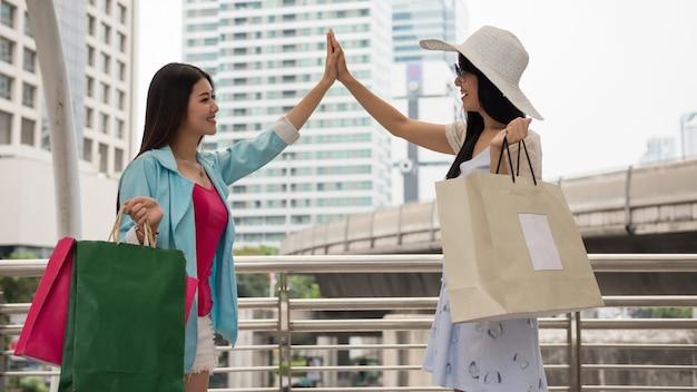 아름다운 아시아 젊은 여성 친구는 많은 상인 가방을 가지고 현대 도시에서 우연히 만난 후 5개의 제스처를 취합니다. 웃는 여자들은 쇼핑몰에서 우연히 만난다.