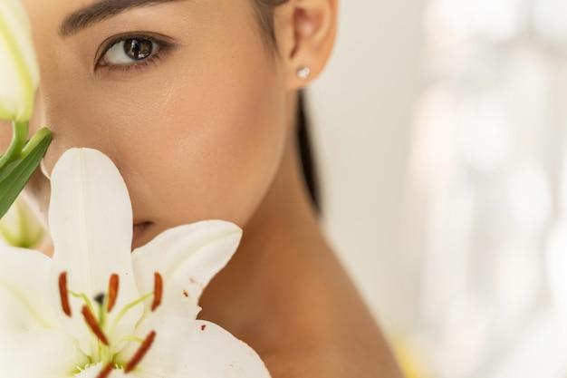아름다운 꽃 냄새를 맡는 아름다운 아시아 젊은 아가씨