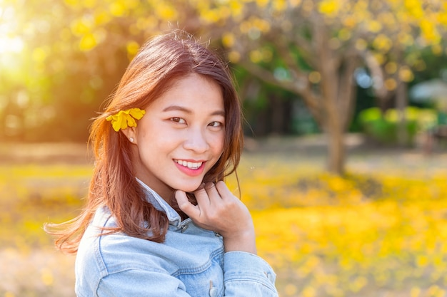 Beautiful asian young teen girl with nature yellow flower autumn.