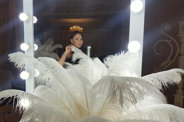 화장 거울 옆에 있는 금색 탁자에 있는 아름다운 아시아 젊은 여성과 장식용 타조 깃털