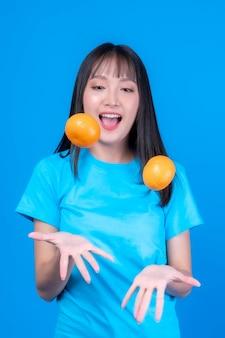 아름다운 아시아 젊은 여성은 머리 스타일을 앞머리로 하고 밝은 파란색 셔츠를 입고 파란색 배경에 격리된 왼손과 오른손 사이에 오렌지를 던지며 즐겁게 놀고 있습니다.