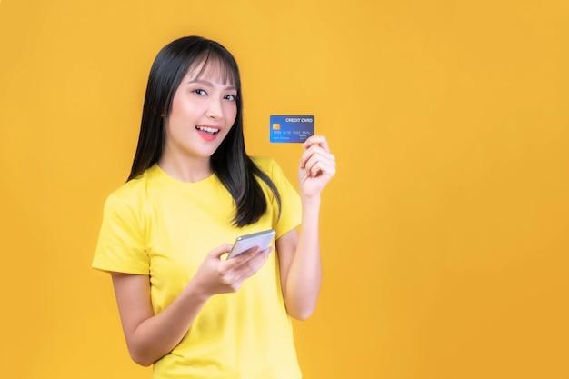 신용카드와 스마트폰을 들고 노란색 셔츠에 앞머리를 한 아름다운 아시아 젊은 여성, 휴대전화는 노란색 배경에서 격리된 유료 온라인 쇼핑을 위해 온라인 뱅킹을 사용합니다.