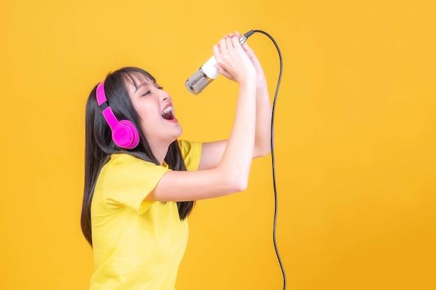 Красивая азиатская молодая женщина милая девушка с челкой прически в желтой рубашке с розовыми наушниками, используя микрофон, чтобы петь песню, изолированную на желтом фоне, скопируйте пространство