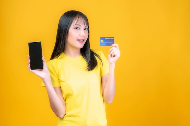 Beautiful asian young woman cute girl with bangs hair style in yellow shirt holding credit card and smartphone ,mobile phone uses a online banking for pay online shopping isolated on yellow background