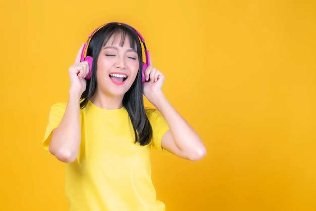 Beautiful asian young woman cute girl with bangs hair style in yellow shirt smiling with pink headphone listen to her favorite song isolated on yellow background , copy space