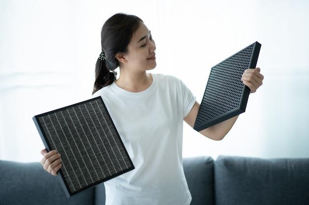 Красивая азиатская молодая женщина, держащая фильтр очистителя воздуха углерода hepa в гостиной, женщина подготавливает фильтр очистителя воздуха, чтобы заменить старый. концепция здравоохранения и хорошего образа жизни.