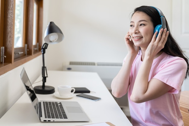 Beautiful asian young woman listening with wireless headphones and working on laptop computer while sitting at the living room at home.
