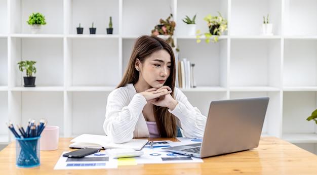 노트북에서 정보를 보고 있는 아름다운 아시아 젊은 여성, 똑똑하고 현대적인 여성 임원, 스타트업 비즈니스 여성, 비즈니스 리더 여성으로 일하는 아시아 비즈니스 여성의 개념 이미지.