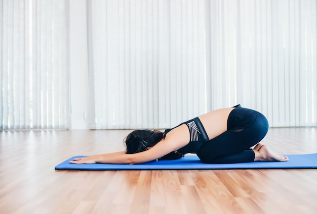 Beautiful asian young woman practices yoga, pilates exercise training at home