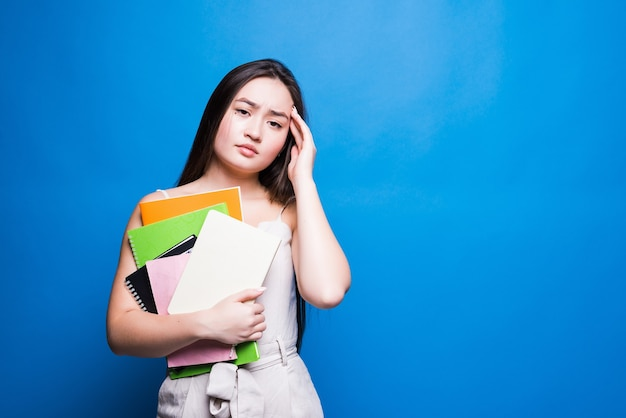 Beautiful asian young woman reading book isolated on the blue wall