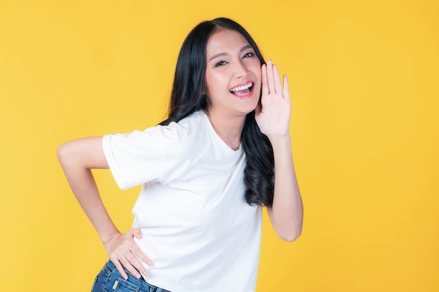 Beautiful asian young woman screams announce the good news or promotion , holding hands near her face with open mouth herald news promotion isolated on yellow background