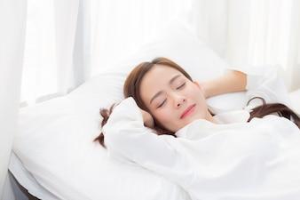 Beautiful asian young woman sleeping lying in bed.