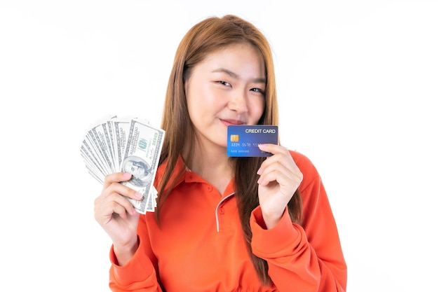 Beautiful asian young woman smiling happily in one hand , held a large amount of us dollars she had obtained from her credit card in her other hand - paying by credit card online shopping concept