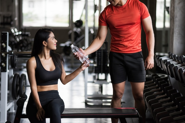 아름 다운 아시아 젊은 여자는 피트니스 체육관에서 그녀의 boyfirend에 의해주는 물 한 병을 가져
