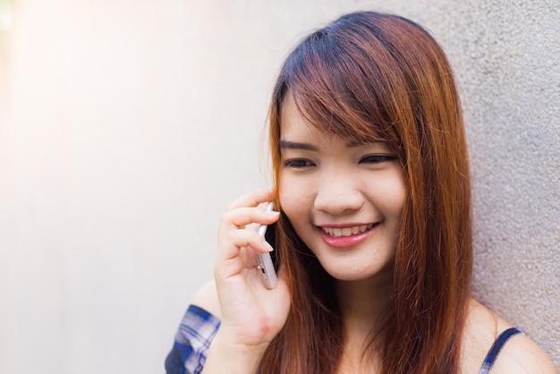 Красивая азии молодая женщина, говорить на мобильном телефоне, над бетонной стеной. стиль цветного тонального фильтра.