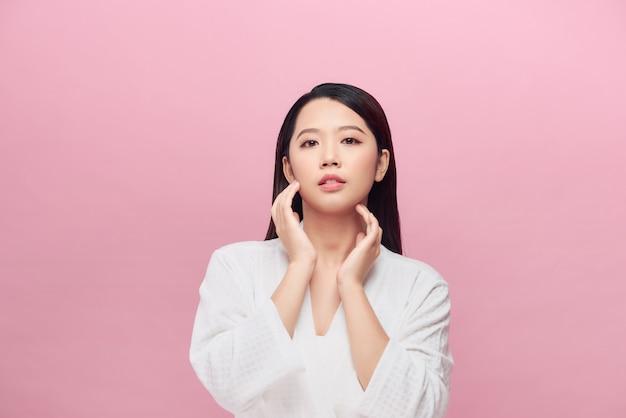 清潔で新鮮な肌で首の笑顔に触れる美しいアジアの若い女性
