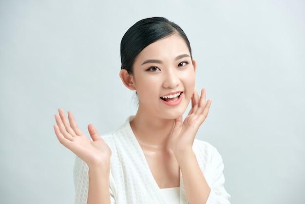 Красивая азиатская молодая женщина трогательно мягкая улыбка щеки с чистой свежей кожей счастья и жизнерадостности с положительными эмоциями