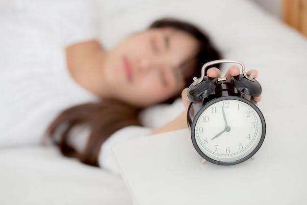 朝目覚まし時計をオフにする美しいアジアの若い女性