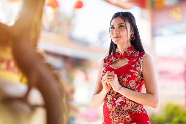 빨간색 전통 중국 치파오를 입고 아름 다운 아시아 젊은 여자, 중국 신사에서 구정 축제 부처님 동상에기도