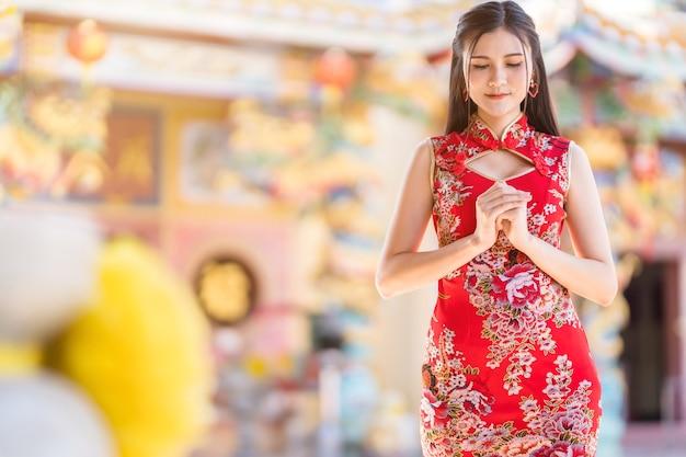 빨간색 전통 중국 치파오를 입고 아름 다운 아시아 젊은 여자, 중국 신사에서 구정 축제에 대 한 부처님 동상에기도 대
