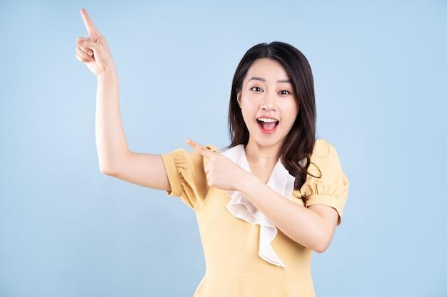 Beautiful asian young woman wearing yellow dress on blue blackground
