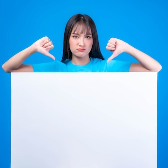 Beautiful asian young woman with bangs hair style in blue t shirt showing her thumb upside down , showing her dislike ,disapproval, and disapproval empty space blank white board on blue background