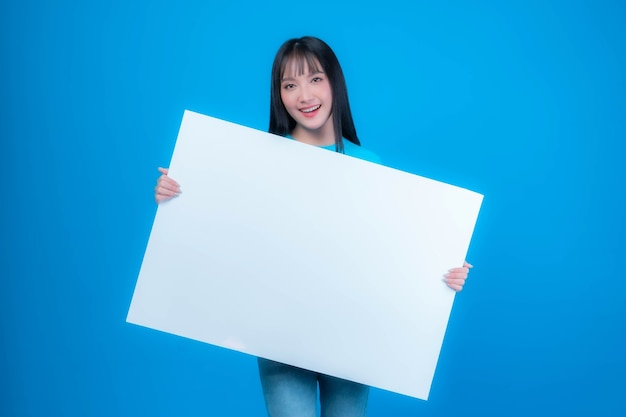 Beautiful asian young woman with bangs hair style in blue t shirt smiling and holding a blank board empty space for advertising banner , white board a blank banner isolated on blue background