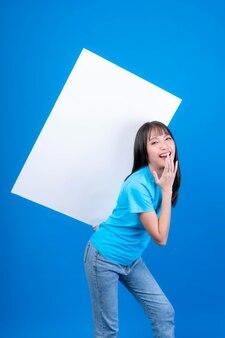 Красивая азиатская молодая женщина с челкой прически в синей футболке улыбается и держит пустую доску пустое место для рекламного баннера, белая доска пустой баннер, изолированные на синем фоне