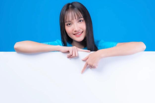 Красивая азиатская молодая женщина с челкой прически в синей футболке улыбается и указывает пальцем на пустое пространство для рекламного баннера, пустое пространство на белой доске, пустой баннер, изолированные на синем фоне