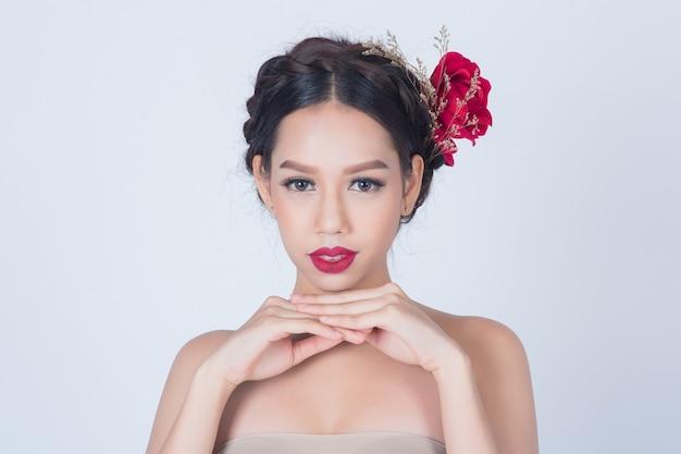 製品とデザインのコピースペースとスキンケアまたは白い背景の上の健康的なコンセプトのためのきれいな新鮮な肌を持つ美しいアジアの若い女性
