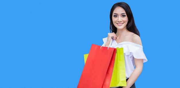 衣料品店に立ちながら笑顔で買い物袋を持つ美しいアジアの若い女性。幸福、消費、販売、人々のコンセプト