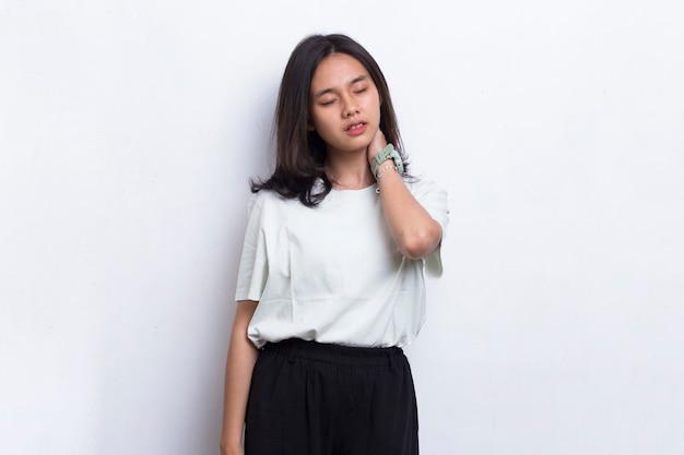 Красивая азиатская молодая женщина с болью в шее и плече, изолированной на белом фоне