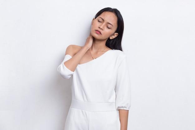 白い背景で隔離の喉の痛みと肩の痛みを持つ美しいアジアの若い女性