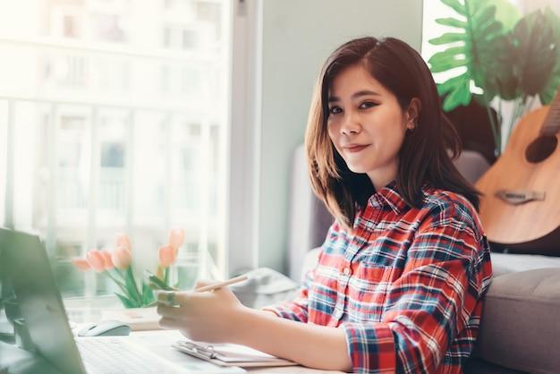 ノートパソコンで自宅で仕事美しいアジアの若い女性